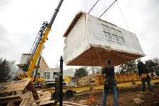 One of nine sections of a modular home is lifted into place with a crane during a PPG Properties construction project on North Benson Road in Fairfield, Conn. on Wednesday, February 22, 2017. The initial assembly of the modules was finished in just one day.
