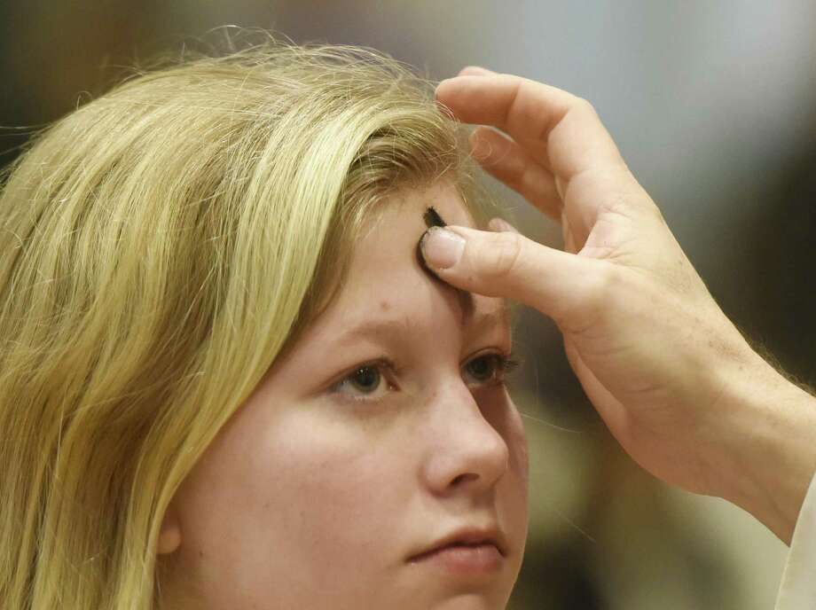Seventh-grader Chloe Dalton receives an ash cross on her forehead during the Ash Wednesday liturgy at Convent of the Sacred Heart in Greenwich last February. Ash Wednesday marks the start of Lent in Christianity. Photo: Tyler Sizemore / Hearst Connecticut Media / Greenwich Time