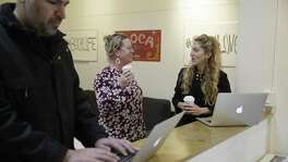 Ashley Breinlinger (right), a senior vice president at BOCA Communications, talks with owner Kathleen Shanahan as Vice President Sammy Totah works at their offices in San Francisco. Breinlinger says the flu season has been so bad that Breinlinger and CEO Kathleen Shanahan have asked staffers when they first start feeling unwell to stay home and not spread their germs.