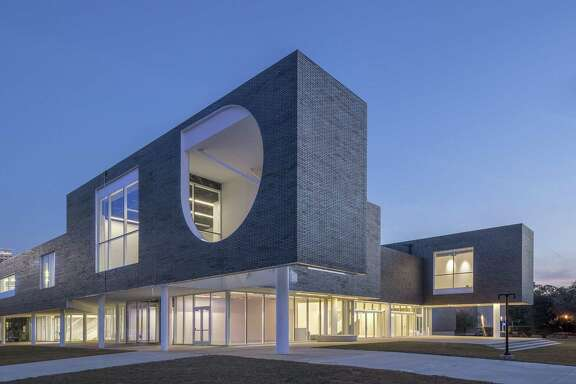 The exterior of Rice University's Moody Center for the Arts, designed by Michael Maltzan, has an upper facade of grey brick and a ground floor of glass.