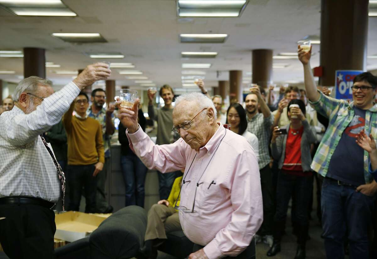 Veteran reporters Carl Nolte and David Perlman lead the newsroom at The San Francisco Chronicle in a toast as the paper celebrates 150 years of operation on Friday January 16, 2015 in San Francisco, Calif.