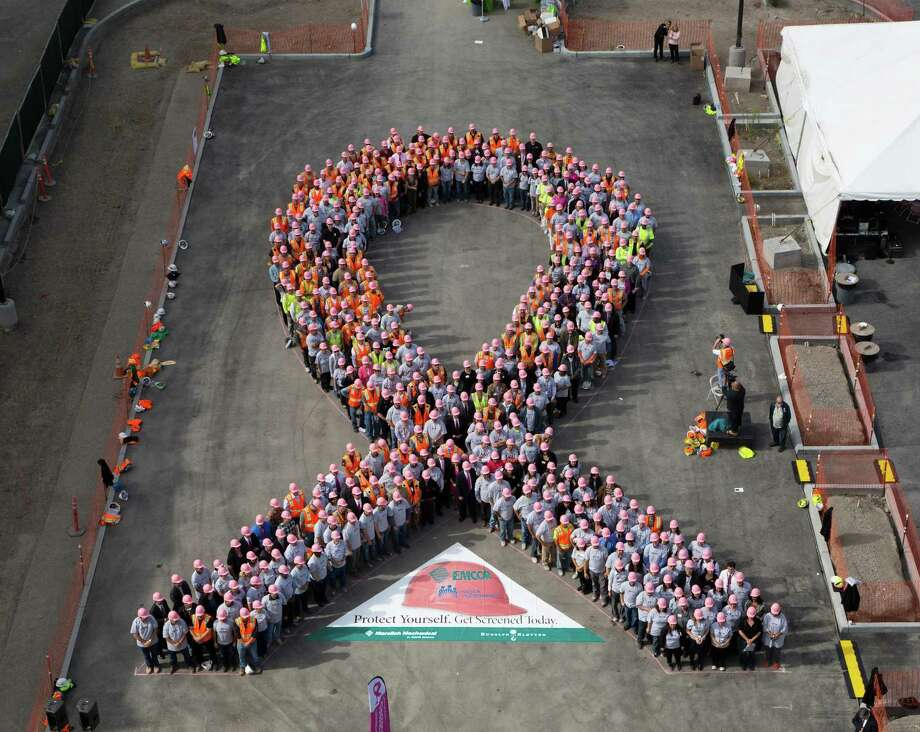 EMCOR Group employees form the breast-cancer awareness logo as part of the Norwalk, Conn.-based giant's Pink Hard Hat campaign. In 2016, Emcor added 2,000 employees to push its total to 31,000 in all. (Photo: Business Wire) Photo: Frederic Neema / Frederic Neema / © 2012 Frederic Neema