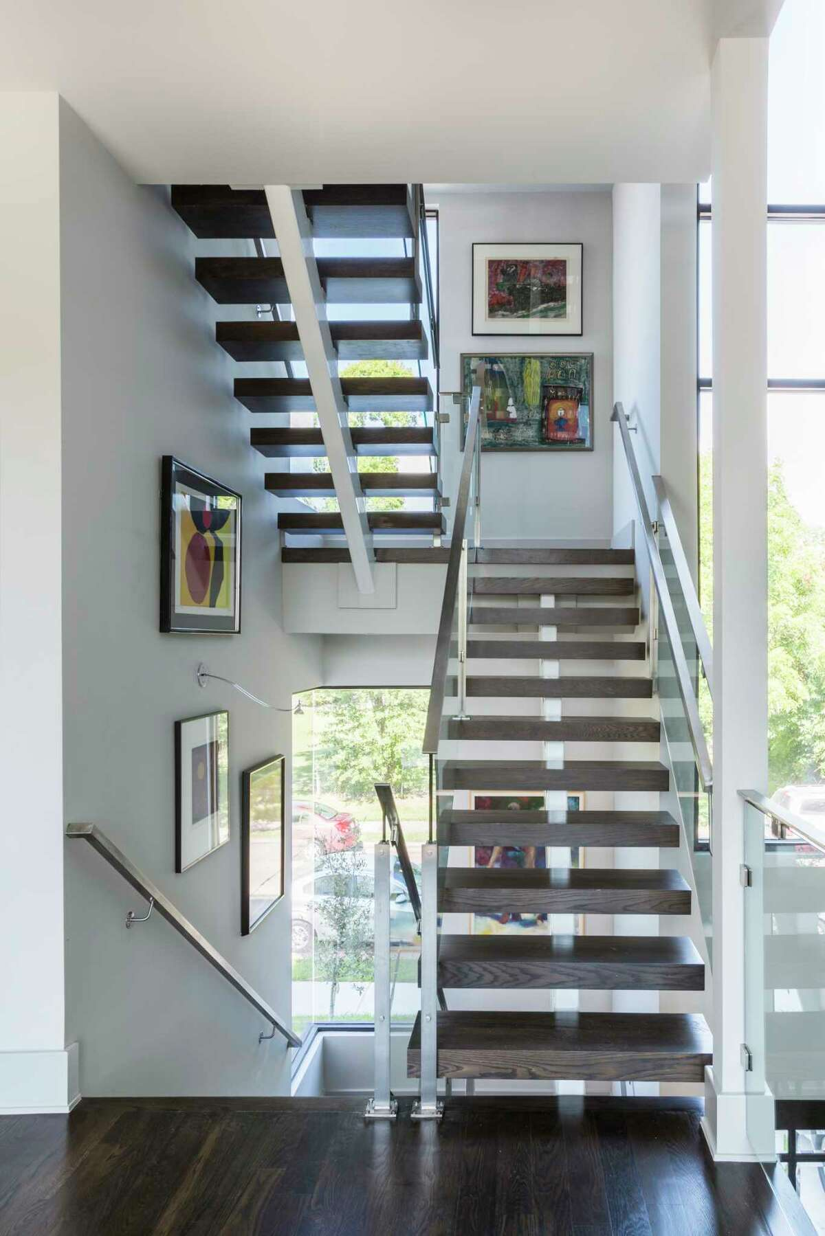 The stairwell is lined with art in the Lampasas Terrace home of Ed and Harriet Reitman.