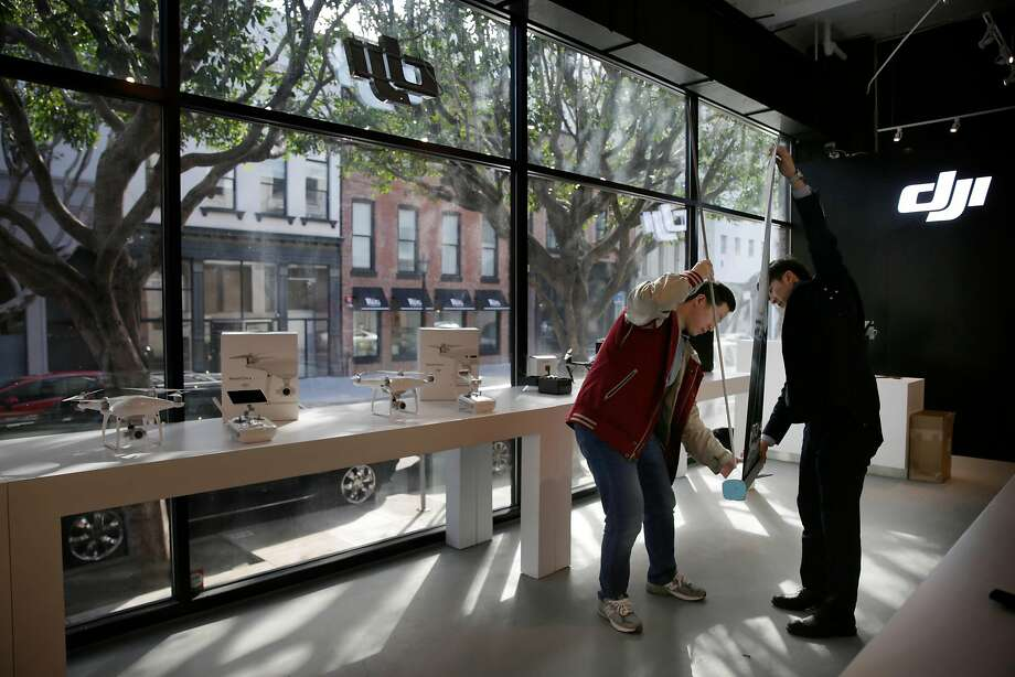 Leon Li, Magic Sky regional manager (left) and Tim Seong, Magic Sky general manager, set up a display while preparing the new DJI drone store on Montgomery Street in San Francisco. Photo: Lea Suzuki, The Chronicle
