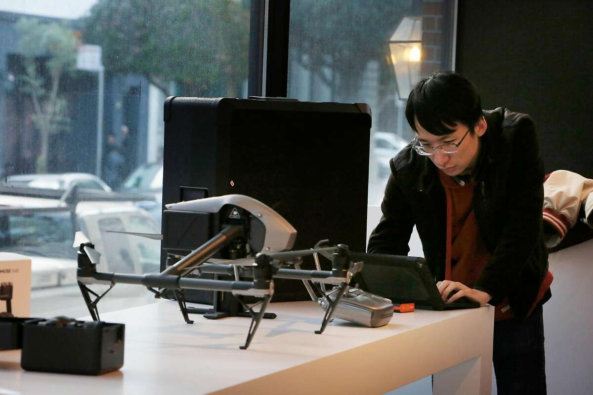 Ken Chen, Magic Sky sales associate, works next to a DJI Inspire drone displayed at the new DJI store on Montgomery Street while preparing the store for it's grand opening on Friday, February 24, 2017 in San Francisco, Calif.