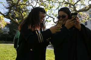 Pam Patino, left, and Beatriz Israde, right, first year students  at University of California, Berkeley takes a picture of flowers using their cell phones on Friday, Feb. 24, 2017, in Berkeley, Calif.