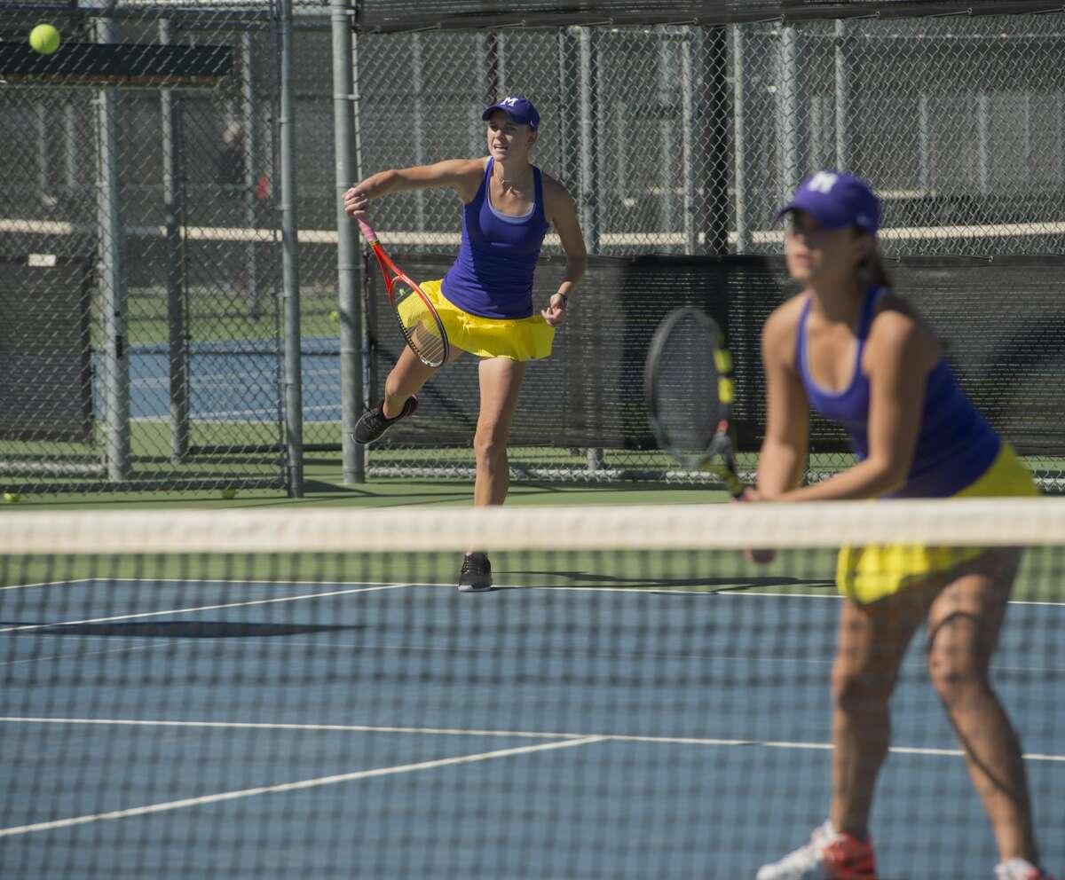 Midland High's Kate Daughety serves Friday 02-24-17 as her doubles partner, Allison Stewart waits on a return during a match at Bush Tennis Center. Tim Fischer/Reporter-Telegram