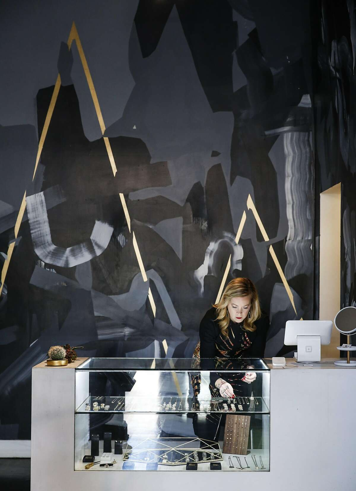 Marie McCarthy, co-owner of Fiat Lux, places jewelry in a display case in front of a mural by Victor Reyes on Friday, Feb. 24, 2017 in San Francisco, Calif.
