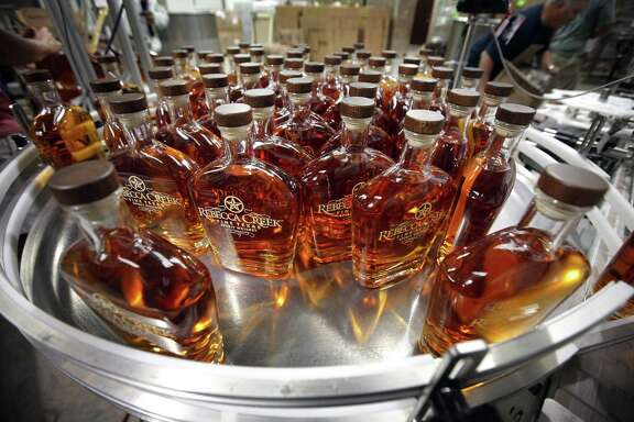 Bottles of whiskey roll off the production line and await to be sealed and packed away.