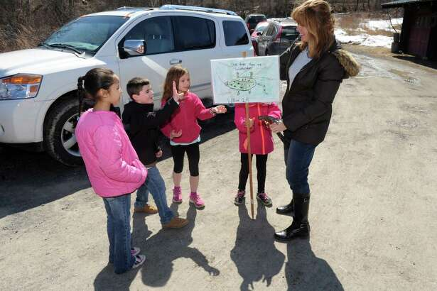 Altamont Elementary School art teacher Trisha Zigrosser, right, and second grade students put up save our salamander signs along Picard Road on Wednesday April 1, 2015 in Altamont, N.Y. (Michael P. Farrell/Times Union)