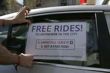 "Michael Morgenstern, left, tapes  a sign on the car reading ""Free Rides!""  before driving around offering people free rides as an alternative to using Uber, on Friday, Feb. 24, 2017, in Berkeley, Calif."