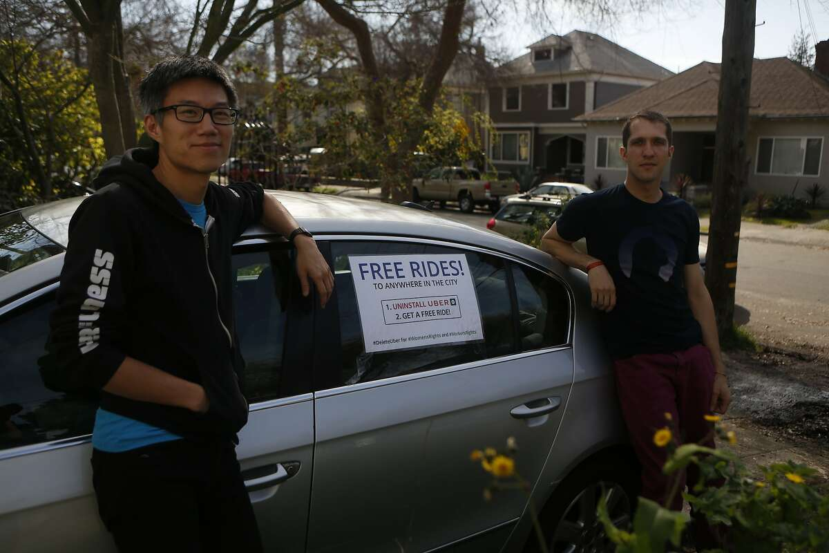 """Ka-Ping Yee, left, and Michael Morgenstern, right, stand in front of their car with a sign reading, Free Rides!"""" before driving around offering people free rides as an alternative to using Uber, on Friday, Feb. 24, 2017, in Berkeley, Calif."""