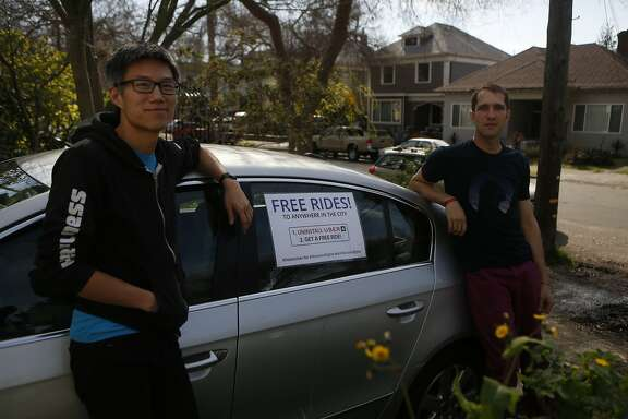 "Ka-Ping Yee, left, and Michael Morgenstern, right, stand in front of their car with a sign reading, Free Rides!""  before driving around offering people free rides as an alternative to using Uber, on Friday, Feb. 24, 2017, in Berkeley, Calif."