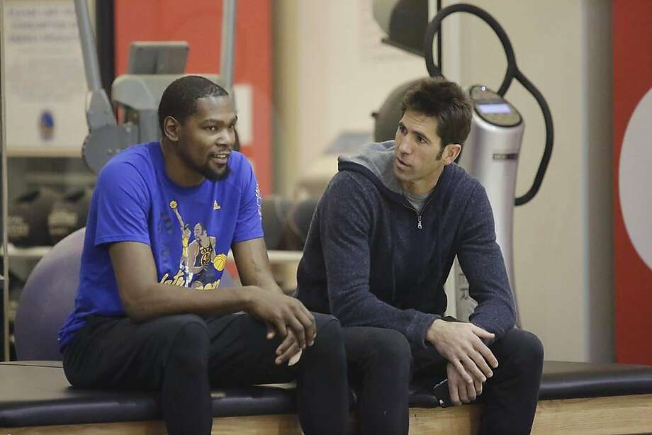 FILE – Kevin Durant and Bob Myers, Golden State Warriors general manager, talk during a Warriors' practice session in Oakland in this Feb. 24, 2017 file photo. On a recent radio show appearance, Myers revealed details of the conversation he had with Durant when the two-time NBA Finals MVP told him he was leaving the team for the Brooklyn Nets. Photo: Lea Suzuki / The Chronicle