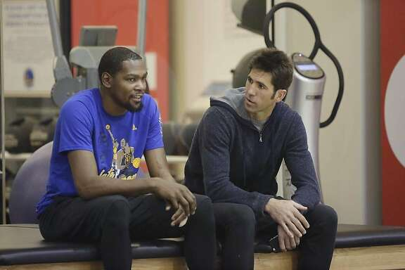 Kevin Durant (l to r) and Bob Myers, Golden State Warriors general manager, talk during a Warriors' practice session on Friday, February 24, 2017 in Oakland, Calif.