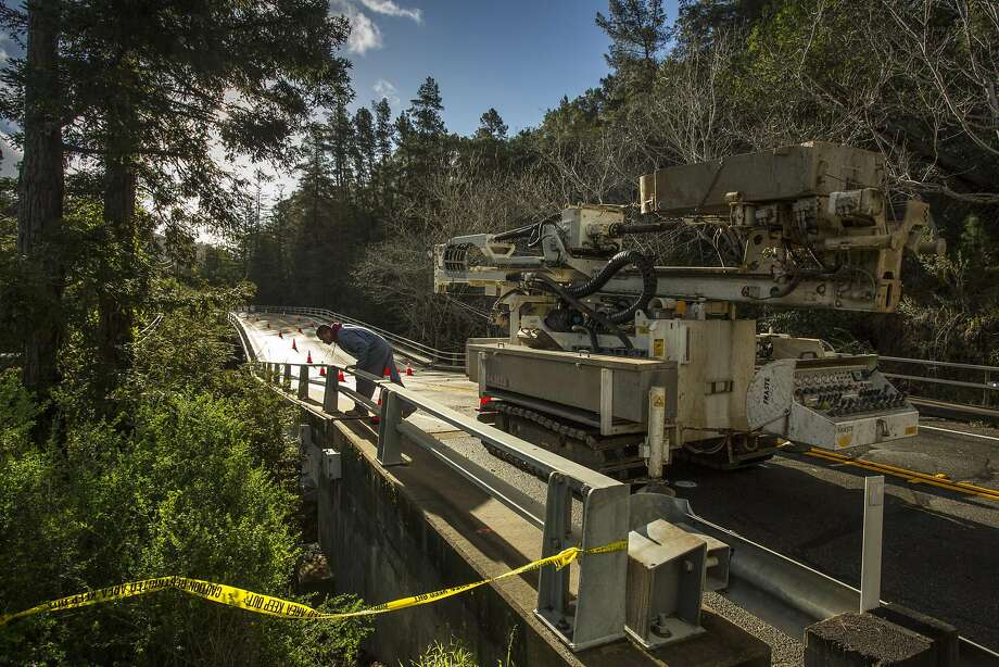 A surveyor Thursday examines the damaged Pfeiffer Canyon Bridge on Highway 1 in Big Sur. The closing of the bridge has left hundreds of residents and workers in the area stranded. Photo: Kodiak Greenwood