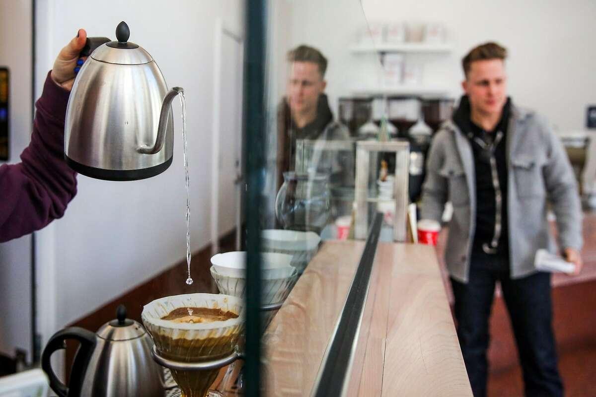 Barista Megan Kepnach (left) makes a pourover coffee while James Faulkner (right) walks through the cafe at Ritual coffee in the Haight neighborhood in San Francisco, California, on Thursday, Feb. 23, 2017.