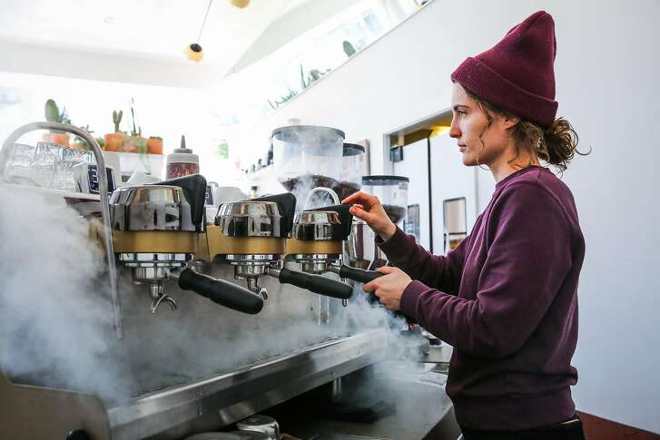 Barista Megan Kepnach demonstrates how they clean the coffee heads with water at Ritual coffee in the Haight neighborhood in San Francisco, California, on Thursday, Feb. 23, 2017.