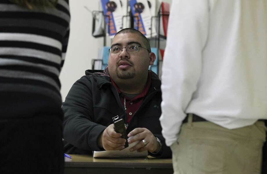 Truancy was decriminalized after the 2014-15 school year but it is an old problem locally. Juvenile Court Case Manager Ramon Olazaran (center) goes over documents with a parent and a student during during a weekly session in the Harlandale School District to discuss truancy on Jan. 14, 2015. Photo: Kin Man Hui /San Antonio Express-News / ©2015 San Antonio Express-News