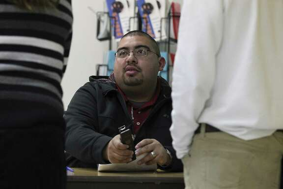 Truancy was decriminalized after the 2014-15 school year but it is an old problem locally. Juvenile Court Case Manager Ramon Olazaran (center) goes over documents with a parent and a student during during a weekly session in the Harlandale School District to discuss truancy on Jan. 14, 2015.