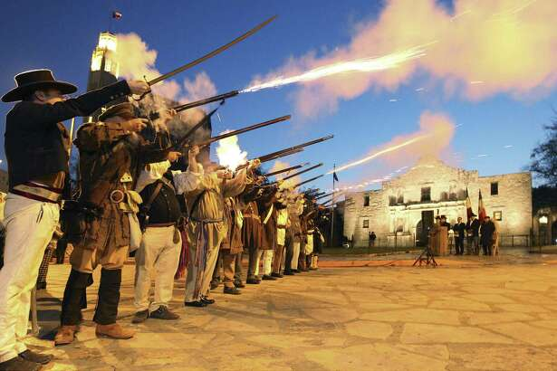 """Members of the San Antonio Living History Association fire muskets on March 7, 2014 in front of the Alamo during the """"Dawn at the Alamo"""" ceremony on the 178th anniversary of the battle for Texas independence. The Legislature is considering more funding for a reimagining of the site. It must be adequate to the task."""