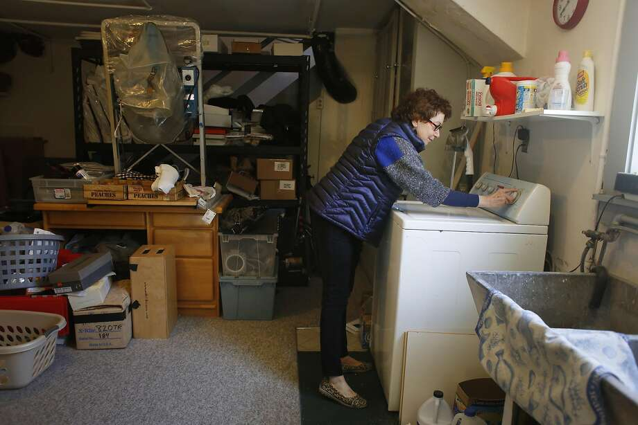 Susan Ansley does a load of wash at her home in Oakland where her utility bills have given her and her husband sticker shock as a recent monthly PG&E bill skyrocketed past $500. Photo: Lea Suzuki, The Chronicle