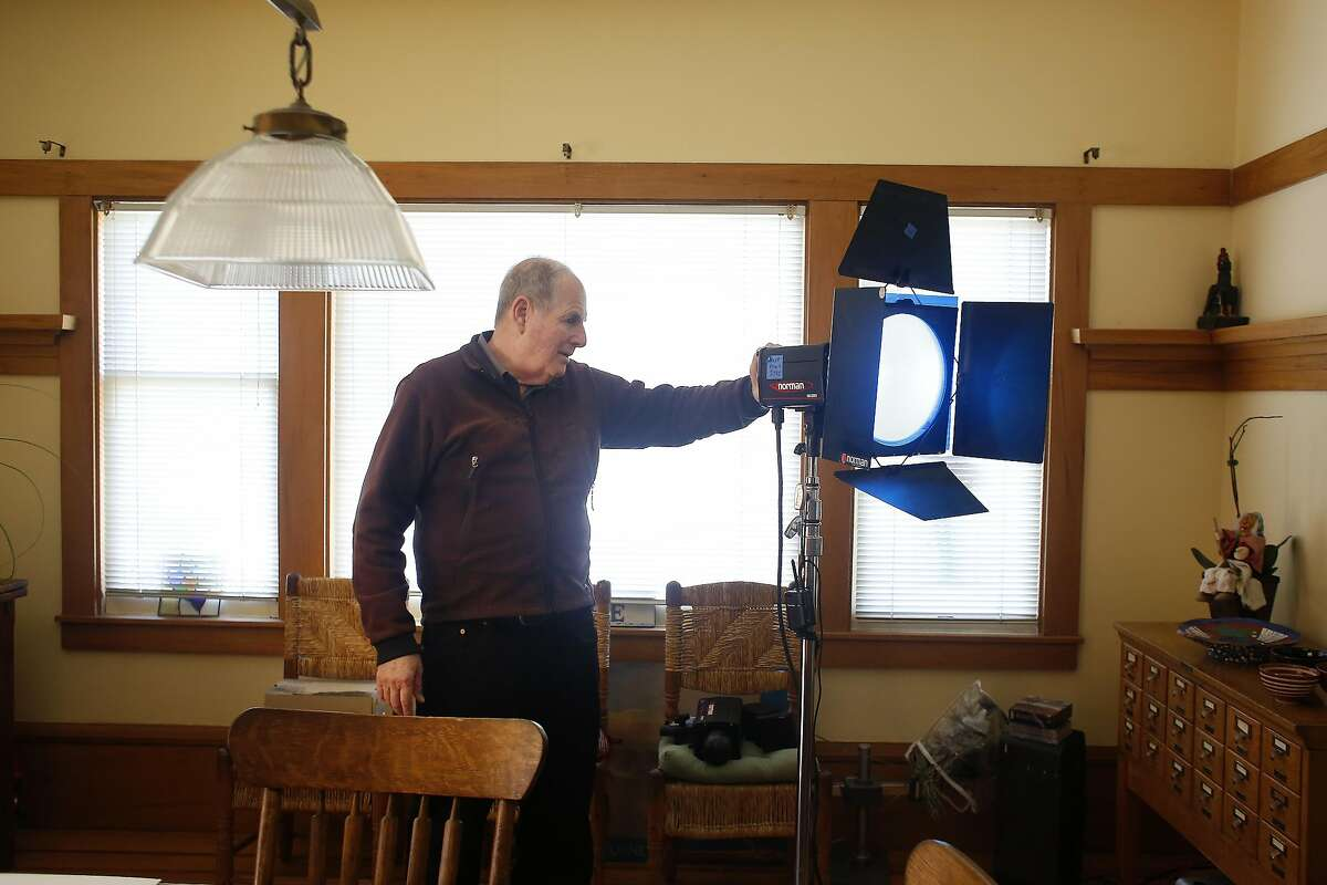Steven Ansley checks a Norman studio light which he will be using for a photo shoot the next day in his dining room on Thursday, February 23, 2017 in Oakland, Calif.