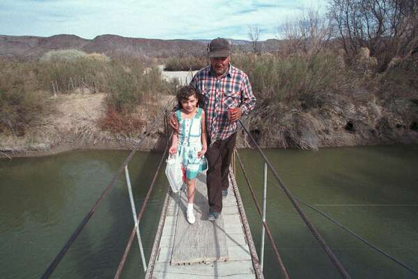 Once upon a time — this photo is from 1998 — there was a bridge that crossed the Rio Grande and connected Candelaria, Texas to San Antonio Del Bravo in Mexico. It's the one Maria Evagelina Garza and her grandfather Vicente dela O crossed in this February 1998 file photo. It no longer exists, thanks to our panic over border security.