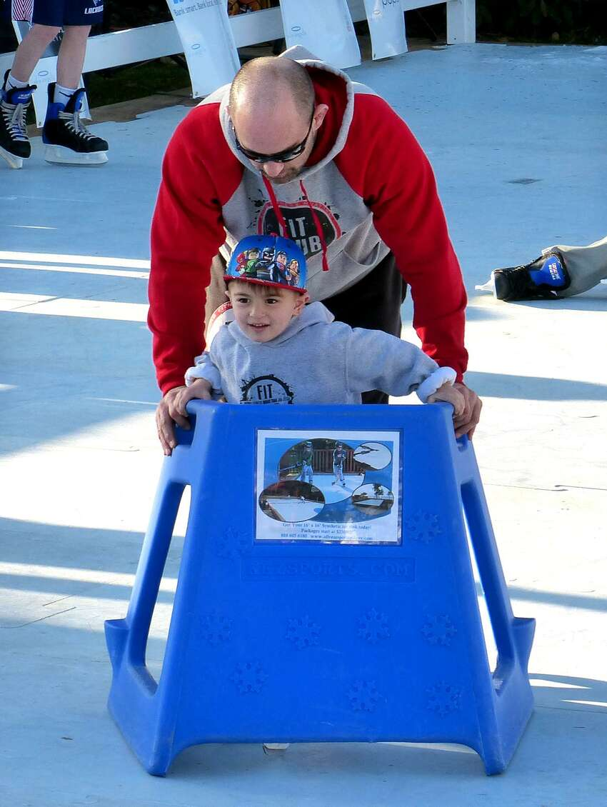 Joe Oppedisano, of Fairfield, helps his son Joejoe, 4, along the ice using a skating aid during LIVFREE and Al's Angels 3-day skating event on Sherman Green in Fairfield, Conn. on Friday Feb. 24, 2017. It is open to the public and will only cost $10 per 30-minute session with ice skate rental included. Money raised by the two charities goes to helping families battle pediatric cancer. Sessions are every half hour with the following times: Saturday - 2/25 from 10am - 9pm and Sunday 2/26 from 10am - 3pm. You can either bring your own ice skates and/or skates will be provided as part of your session fee.