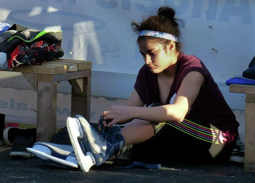 Kylie Hernandez, 14, of Fairfield, puts on her skating before taking part in LIVFREE and Al's Angels 3-day skating event on Sherman Green in Fairfield, Conn. on Friday Feb. 24, 2017. It is open to the public and will only cost $10 per 30-minute session with ice skate rental included. Money raised by the two charities goes to helping families battle pediatric cancer. Sessions are every half hour with the following times: Saturday - 2/25 from 10am - 9pm and Sunday 2/26 from 10am - 3pm. You can either bring your own ice skates and/or skates will be provided as part of your session fee.