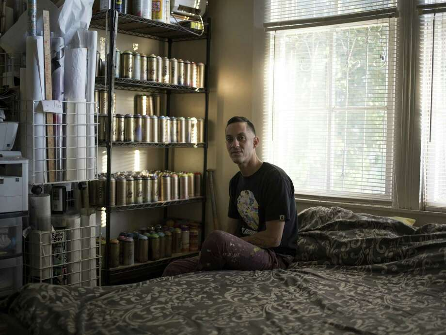 Street artist Scotch! poses for a portrait at his home. The shelves behind him are filled with hundreds of spray paint cans organized by color. Photo: Matthew Busch /For The San Antonio Express-News / © Matthew Busch