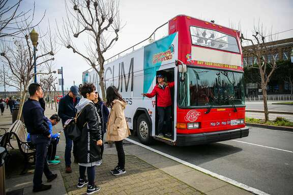 Tour guide Rey Zegri (right,red jacket) hops off a City Sightseeing bus tour to make a stop and chat with customers in San Francisco, California, on Wednesday, Feb. 22, 2017.