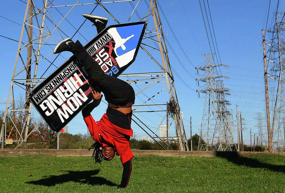 Eric Mayo brings a breakdancing move into his sign spinning while demonstrating his moves at the Danny Jackson Family Bark Park, Tuesday, Feb. 21, 2017, in Houston. The Houston spinners are on their way to the 2017 AArrow Sign Spinners World Championship in Las Vegas this weekend. ( Mark Mulligan / Houston Chronicle ) Photo: Mark Mulligan, Staff / © 2017 Houston Chronicle