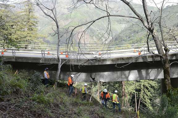 In this Wednesday, Feb. 22, 2017 photo, Caltrans engineers evaluate storm damage near a large crack where the Pfeiffer Canyon Bridge is sagging on Highway 1 in Big Sur, Calif. The bill to repair California�s roadways hammered by floods and rockslides in an onslaught of storms this winter has reached nearly $600 million, more than double what the state budgeted for such emergencies, and the costs are mounting for other badly damaged infrastructure just two months into 2017.  (David Royal /The Monterey County Herald via AP)