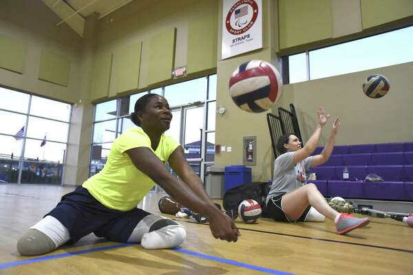 Kari Miller, left, a military veteran who lost her legs to a drunk driver in an accident, and Lindsay Clark, who lost a leg to a birth defect, practice their sitting volleyball technique at Morgan's Wonderland on Thursday, Feb. 23, 2017.