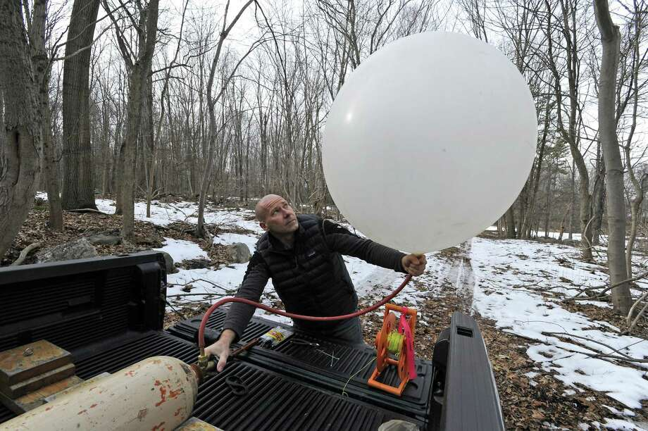 Phil Rydel of All-Points Technology, a consulting firm out of Killingworth, Conn. inflates a balloon on Feb. 21, 2017. The town of New Canaan is conducted a balloon test in the area where a communications tower will be built on property owned by Aquarion at the Laurel Reservoir in North Stamford. The information gathered about the sight lines from the balloon test will be reviewed and presented at a public town meeting. Photo: Matthew Brown / Hearst Connecticut Media / Stamford Advocate