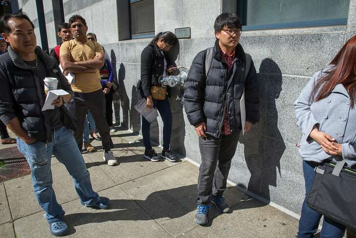 Second from right: Mike Lee, from South Korea, and others wait in line to go inside the U.S. Citizenship & Immigration Service building located at 630 Sansome Street on Thursday, Feb. 23, 2017, in San Francisco, Calif. Lee, a molecular biology student at UC Berkeley, said he was going in for a naturalization interview.