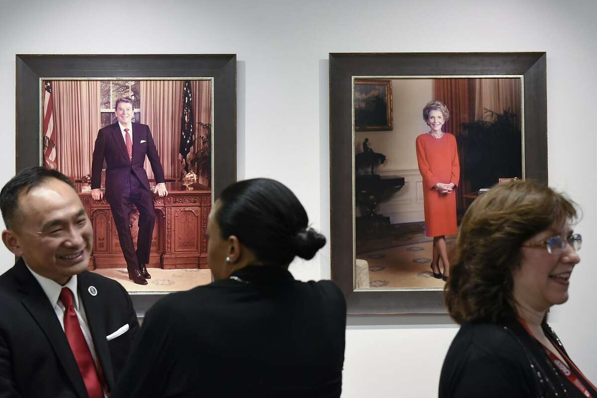 Convention-goers chat in front of portraits of Ronald and Nancy Reagan at the California Republican Party headquarters in Sacramento.