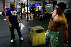 Michael Flores lifts a dumbbell during the first week of the Crossfit Open at Crossfit Beaumont on Friday evening. Athletes at Crossfit gyms around the world complete the same workout each weekend for five weeks in friendly competition and the chance to advance to larger competitions.  Photo taken Friday 2/24/17 Ryan Pelham/The Enterprise
