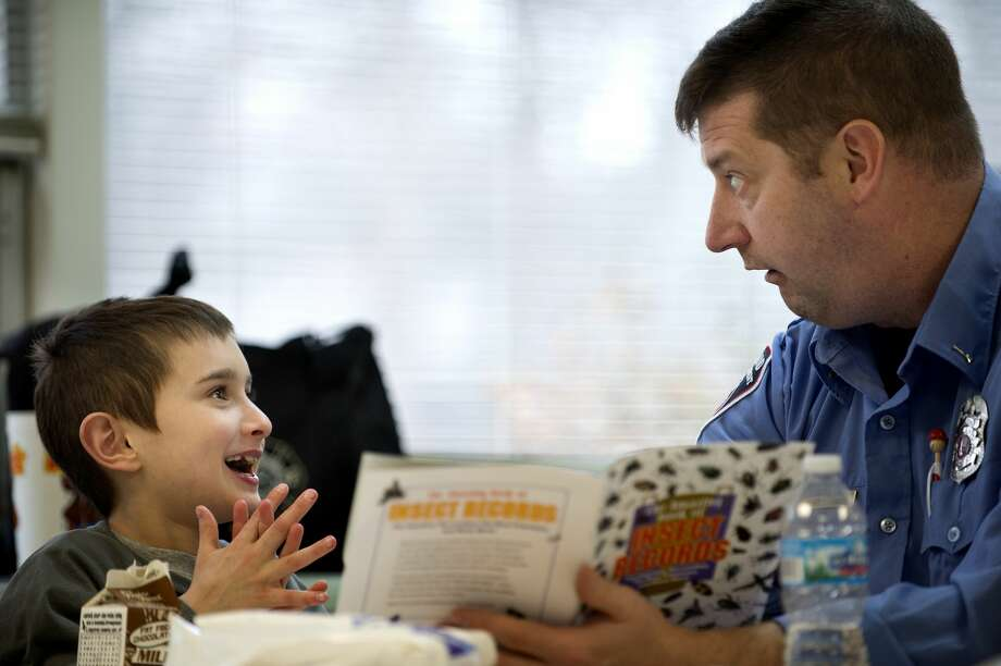 Chestnut Hill second-grader Joe Bishop, left, jokes around with his reading partner Bob Arnold during the Big Brothers Big Sisters Lunchbox Learners program Wednesday afternoon. Thirteen volunteers from Big Brothers Big Sisters sat with students, primarily in first through third grade, once a week for an hour to help students practice reading. Photo: Brittney Lohmiller/Midland Daily News