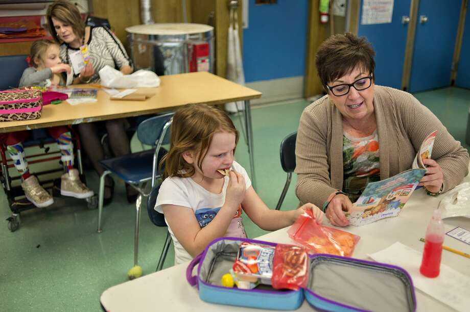 Chestnut Hill third-grader Jillian Mohr, from left, reads with Christie Hill while first-grader Kyra Bensal eats her lunch and listens to Ann Craig read aloud during the Big Brothers Big Sisters Lunchbox Learners program Wednesday afternoon. Thirteen volunteers from Big Brothers Big Sisters sat with students, primarily in first through third grade, once a week for an hour to help students practice reading. Photo: Brittney Lohmiller/Midland Daily News