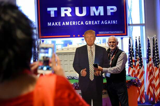 Jessica White of Lemon Cove, CA takes a picture of her husband Mike White as he stands with a cardboard cutout of Trump during the California Republican Party's 2017  Organizing Convention in Sacramento, CA, on Friday February 24, 2017.