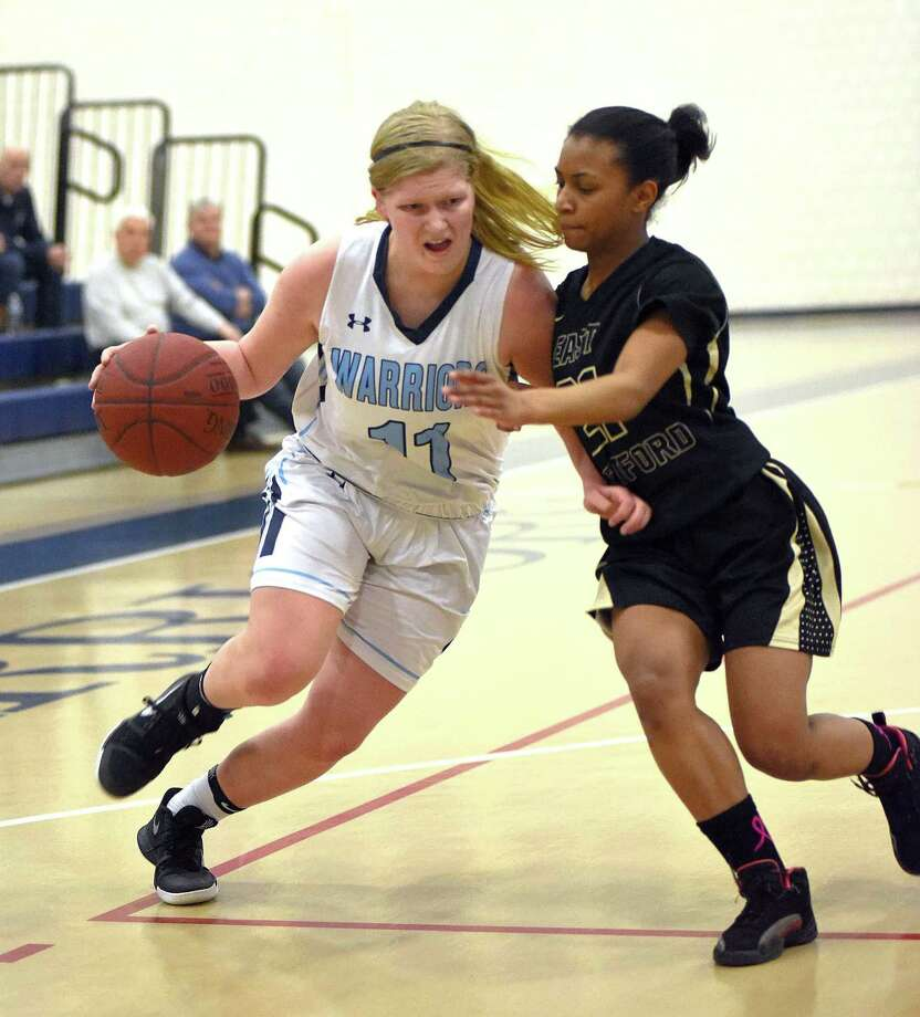 Wilton's Claire Gulbin, left, drives past East Hartford defender Imani Muhammad in the first quarter of Friday's game. Photo: John Nash / Hearst Connecticut Media / Norwalk Hour