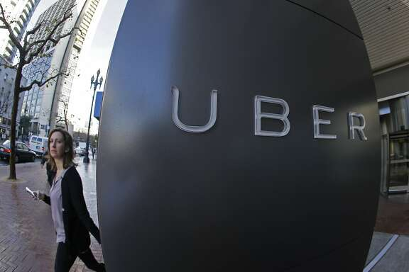FILE - In this file photo taken Tuesday, Dec. 16, 2014, a woman walks past the company logo of the internet car service, Uber, in San Francisco, USA. Uber's chief executive ordered an urgent investigation Monday Feb. 20, 2017, into a sexual harassment claim made by a female engineer who alleged her prospects at the company evaporated after she complained about advances from her boss.  (AP Photo/Eric Risberg, FILE)
