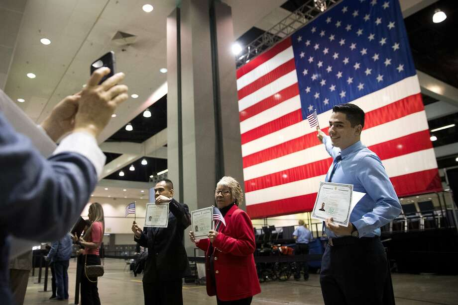 FILE - In this Wednesday, Feb. 15, 2017, file photo, Erik Danialian, a 21-year-old immigrant from Iran, poses with his U.S citizenship certificate in front of a large U.S. flag after a naturalization ceremony at the Los Angeles Convention Center, in Los Angeles. Since Trump's immigration enforcement order and travel ban, immigrants have been rushing to prepare applications to become Americans. Advocates in Los Angeles, Maryland and New York catering to diverse immigrant communities from Latin America, Asia and the Middle East all said they've been fielding a rising number of questions about how to become a U.S. citizen. (AP Photo/Jae C. Hong, File) Photo: Jae C. Hong, Associated Press