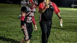 Texas Legacy running back Amanda Lozano walks off the field with coach Gibby Alvarado.