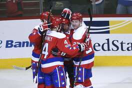 Washington Capitals right wing Justin Williams (14) celebrates his third-period goal with teammates Jay Beagle (83), Taylor Chorney (4) and Karl Alzner (27) as Edmonton Oilers center Leon Draisaitl (29) skates past during an NHL hockey game, Friday, Feb. 24, 2017, in Washington. The Capitals won 2-1. (AP Photo/Molly Riley)