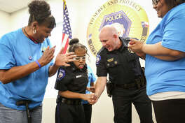 Make-A-Wish recipient Lauryn Williams is sworn in as an honorary Conroe police officer by Philip Dupuis, Conroe Chief of Police, as her grandmother Jackie Anderson and mother LaCoshia Williams applaud on Monday, Nov. 14, 2016, at the Conroe Police Department.