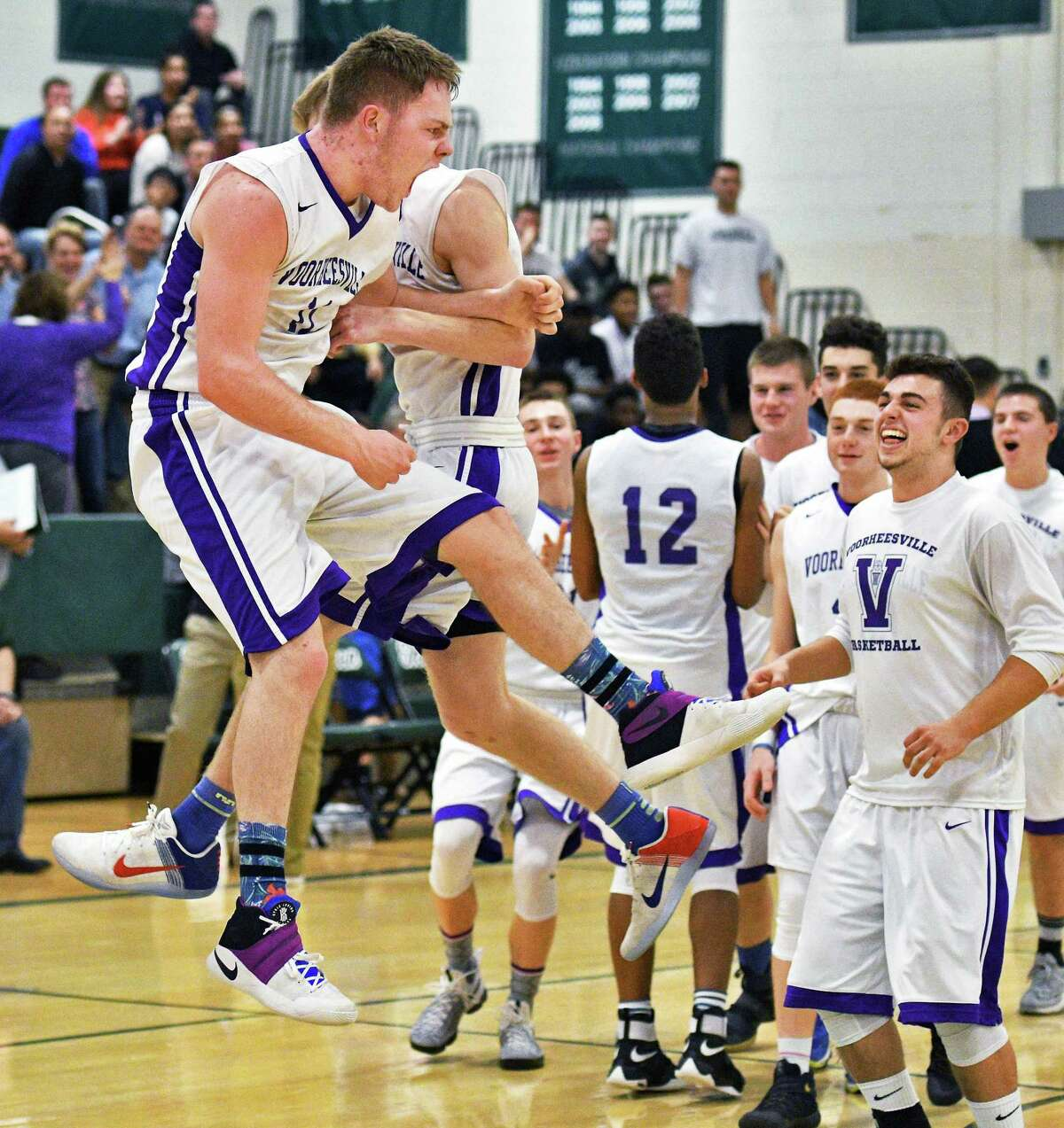 Voorheesville's #11 Ryan Daly and team mates celebrate his tie-breaking winning shot as the best Broadalbin-Perth in their Class B quarterfinal at Shenendehowa High Friday Feb. 24, 2017 in Clifton Park, NY. (John Carl D'Annibale / Times Union)