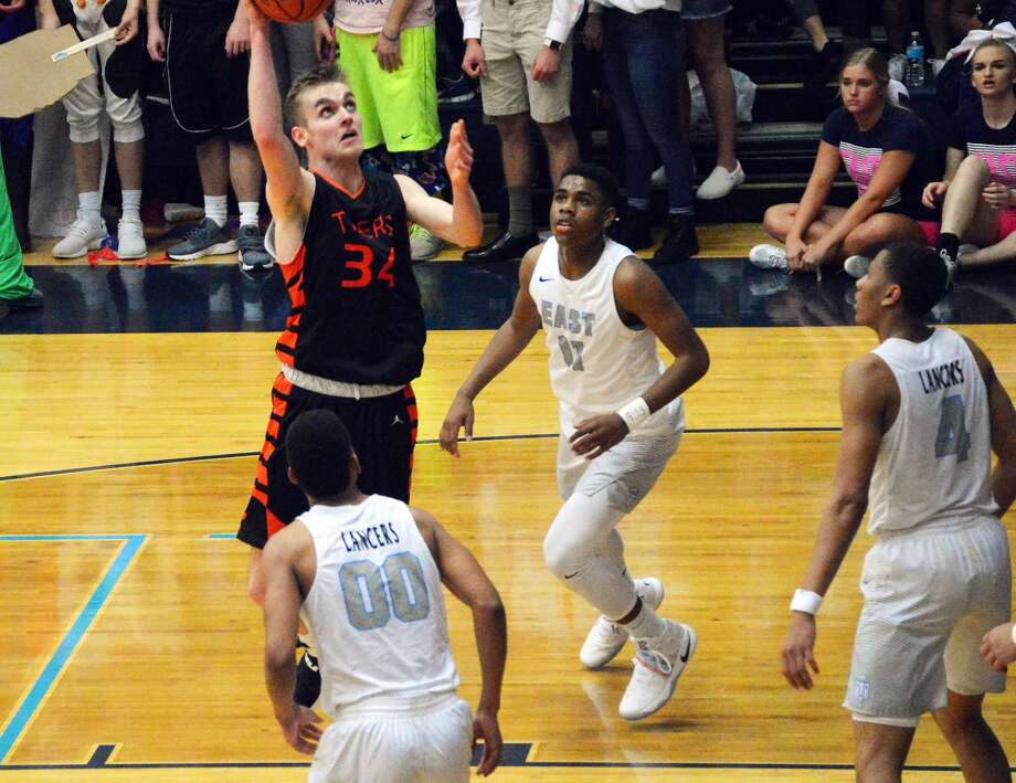 Edwardsville junior forward Caleb Strohmeier hits a shot in the lane with three Belleville East defenders in the vicinity in second-quarter action on Friday in Belleville.